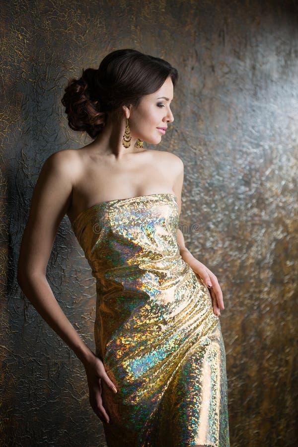 Mujer hermosa joven en vestido del oro de la tarde imágenes de archivo libres de regalías