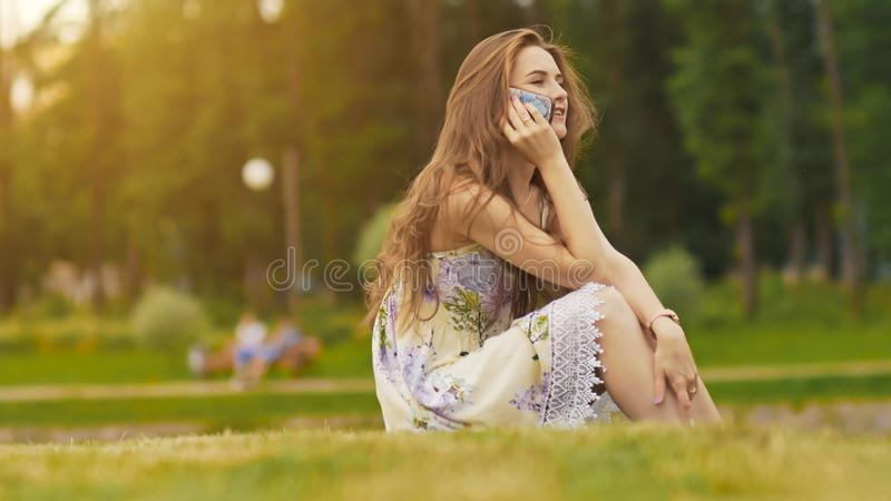 Mujer hermosa joven en vestido del verano con el pelo largo que se sienta en hierba en parque verde y que habla en el teléfono, s fotografía de archivo