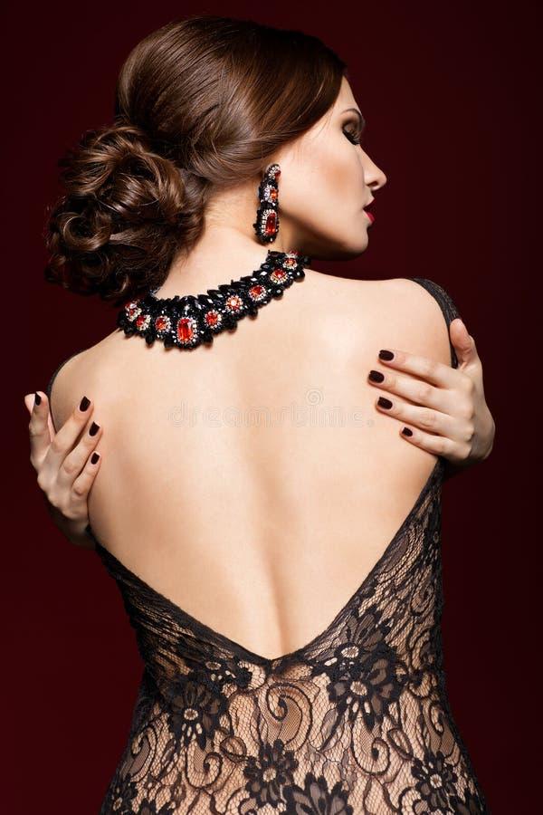 Mujer hermosa joven en vestido negro del lado trasero en el marsala c fotografía de archivo libre de regalías