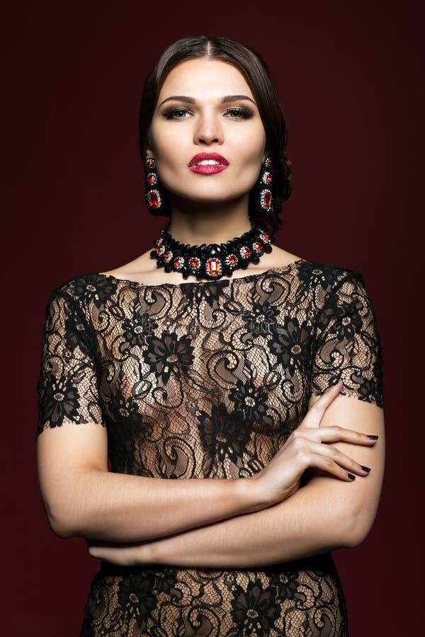Mujer hermosa joven en vestido negro en fondo del color del marsala imagenes de archivo