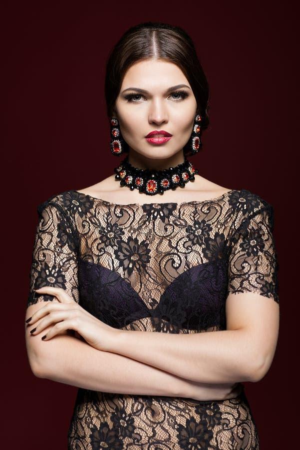 Mujer hermosa joven en vestido negro en fondo del color del marsala imagen de archivo libre de regalías