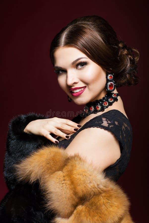 Mujer hermosa joven en vestido negro en fondo del color del marsala foto de archivo