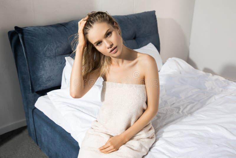 Mujer hermosa joven envuelta para arriba con la toalla de baño que se sienta en cama y la mirada foto de archivo libre de regalías