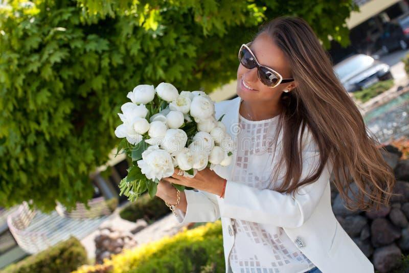 Mujer hermosa joven feliz con un ramo de peonías blancas fotografía de archivo