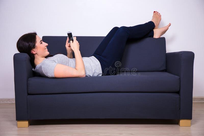 Mujer hermosa joven feliz que miente en el sofá y que usa el teléfono elegante fotografía de archivo