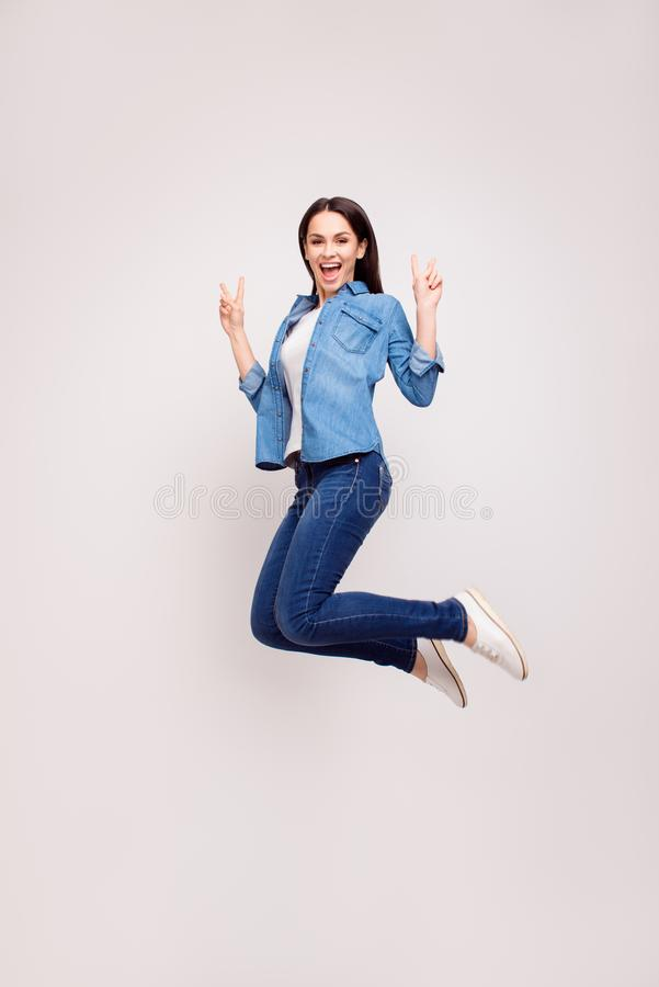 Mujer hermosa joven positiva en la ropa informal que salta para arriba y imagen de archivo libre de regalías
