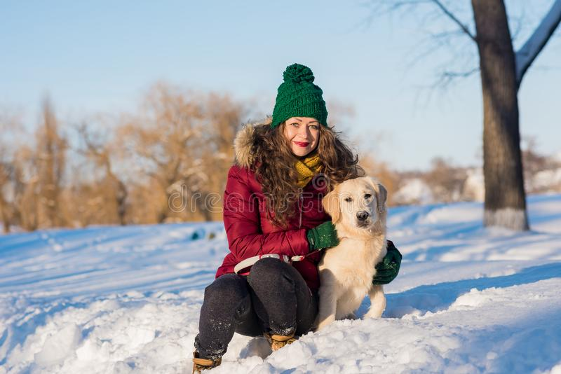 Mujer hermosa joven que abraza el perro del golden retriever foto de archivo libre de regalías