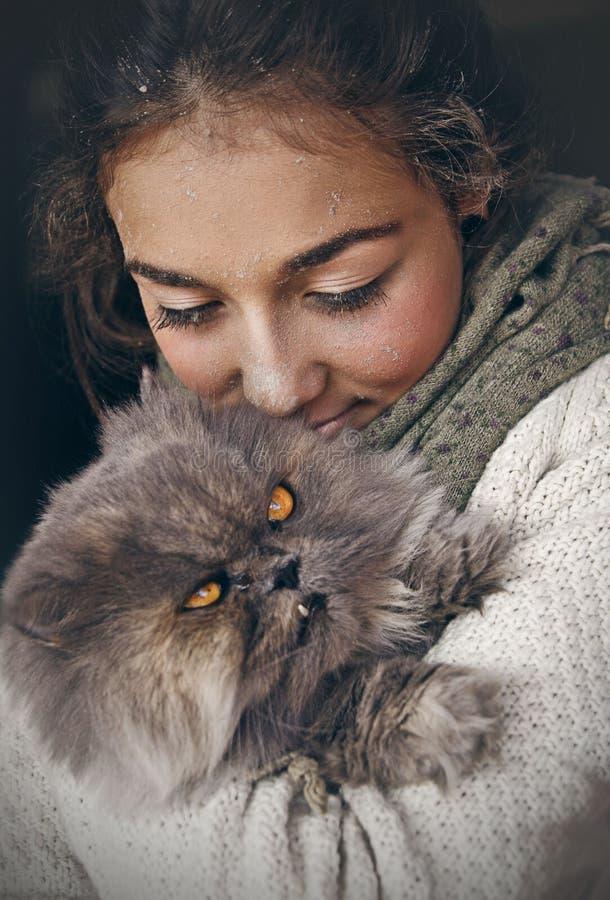 Mujer hermosa joven que abraza su gato persa, llevando una bufanda alrededor de su cuello en un fondo negro fotos de archivo