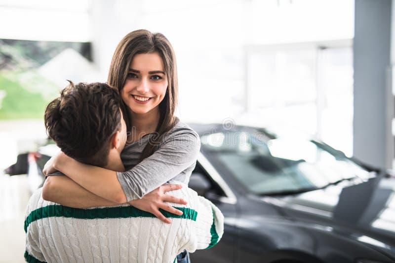 Mujer hermosa joven que abraza sus gracias del novio por el nuevo coche fotos de archivo