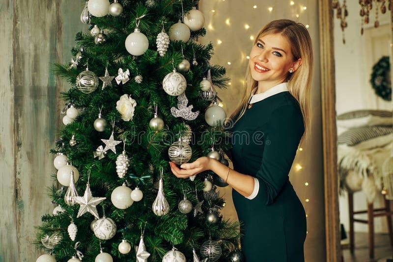 Mujer hermosa, joven que adorna un árbol de navidad fotografía de archivo libre de regalías