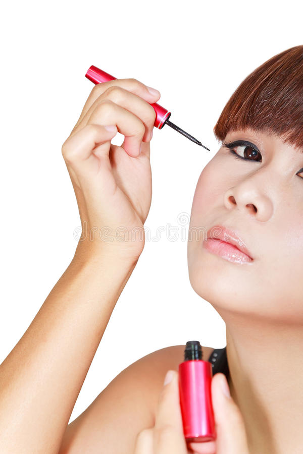 Mujer hermosa joven que aplica lápiz de ojos fotografía de archivo libre de regalías