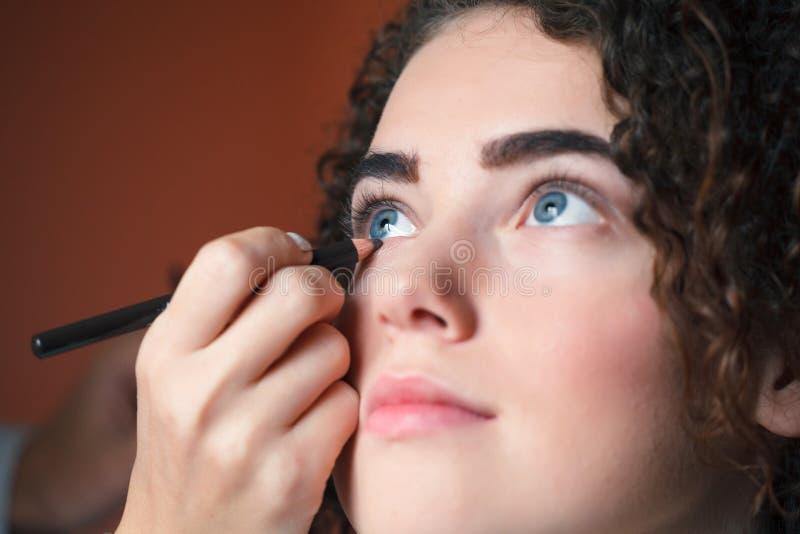 Mujer hermosa joven que aplica lápiz de ojos en el párpado con el lápiz imagen de archivo