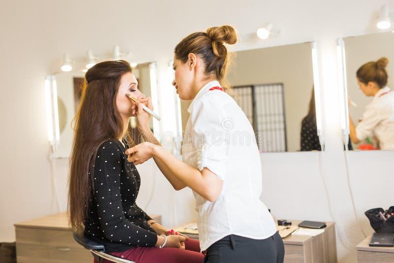 Mujer hermosa joven que aplica maquillaje del artista de maquillaje fotografía de archivo libre de regalías
