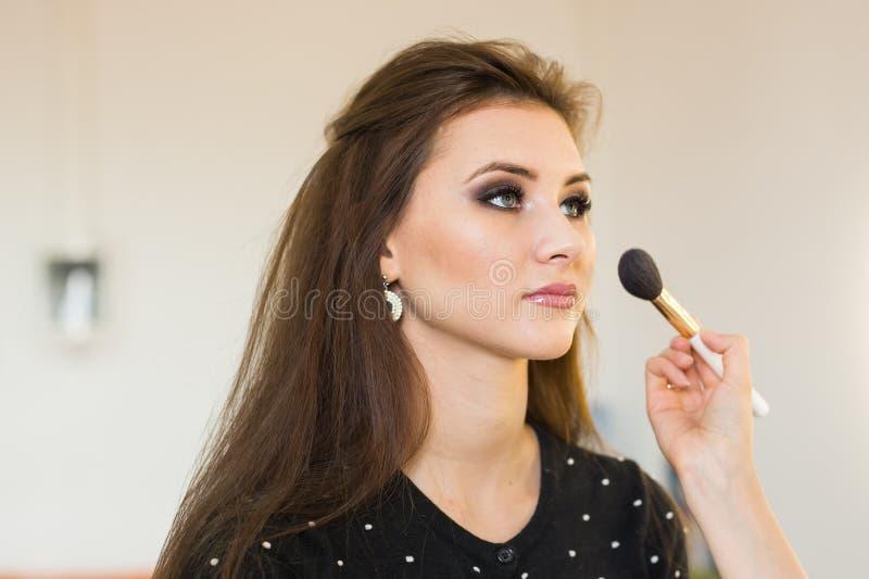 Mujer hermosa joven que aplica maquillaje del artista de maquillaje fotos de archivo libres de regalías