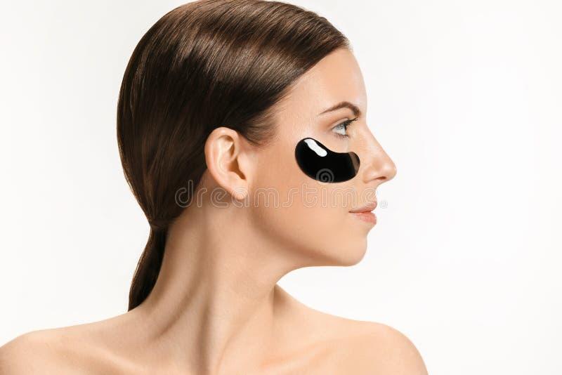 Mujer hermosa joven que aplica una máscara para la cara del fango negro terapéutico Balneario - 7 imagenes de archivo