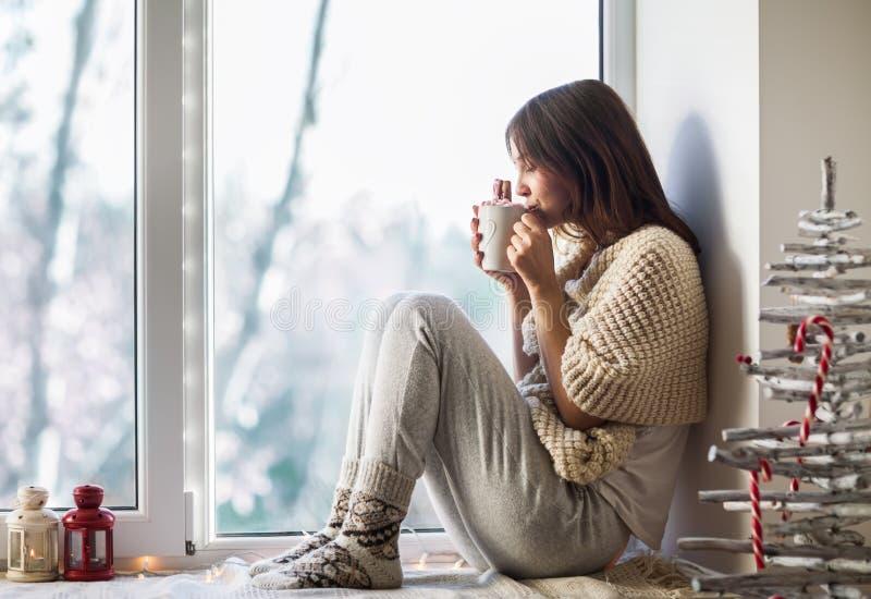 Mujer hermosa joven que bebe el café caliente que se sienta en travesaño de la ventana imagenes de archivo