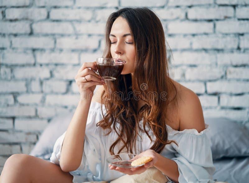 Mujer hermosa joven que bebe el caf? caliente que se sienta en cama y que disfruta de su buena ma?ana fotos de archivo libres de regalías