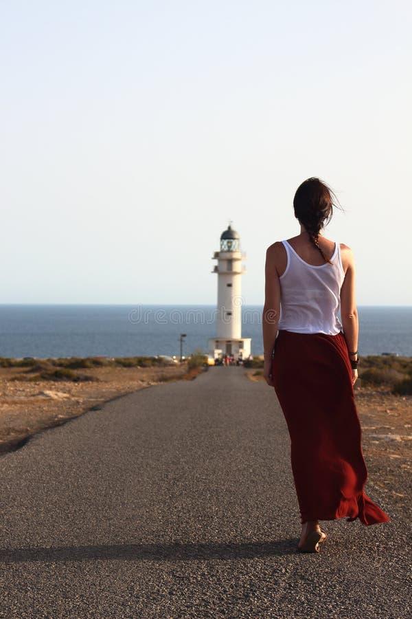 Mujer hermosa joven que camina lentamente al faro de Cap de Barberia durante una puesta del sol asombrosa del verano imagenes de archivo