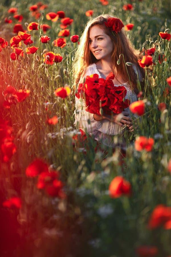 Mujer hermosa joven que camina y que baila a través de un campo de la amapola en la puesta del sol imagen de archivo libre de regalías