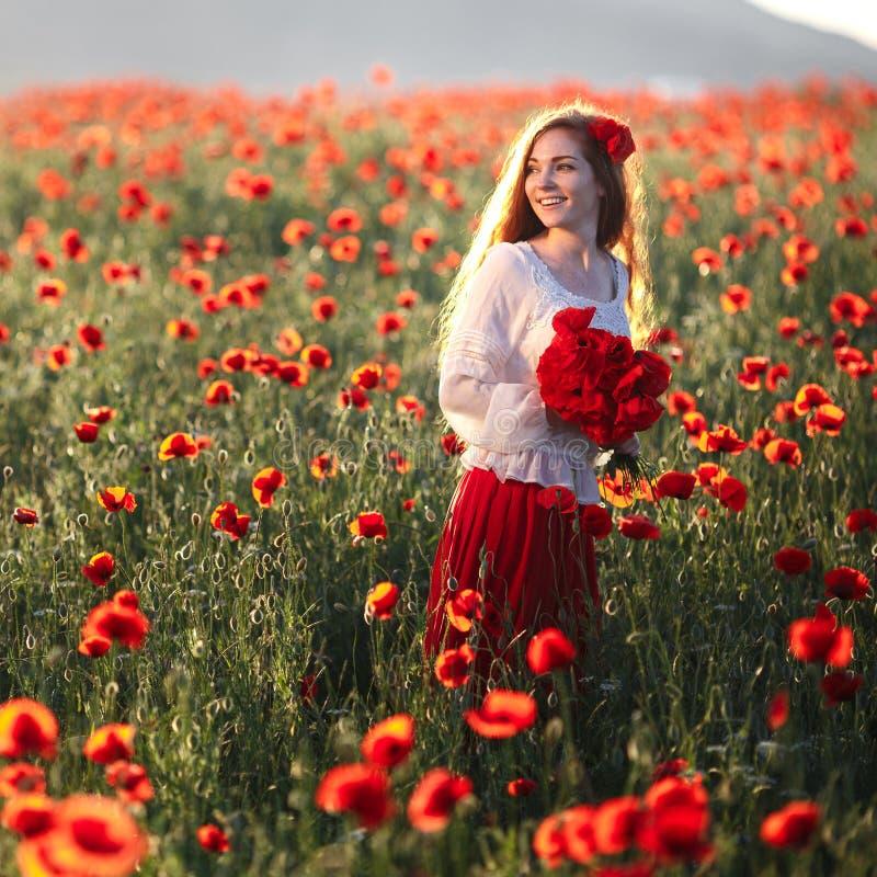 Mujer hermosa joven que camina y que baila a través de un campo de la amapola en la puesta del sol fotos de archivo