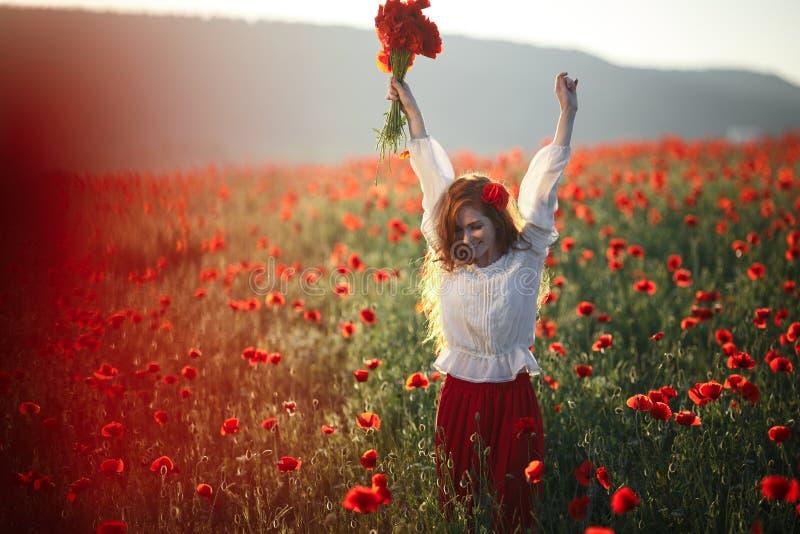 Mujer hermosa joven que camina y que baila a través de un campo de la amapola en la puesta del sol imagenes de archivo