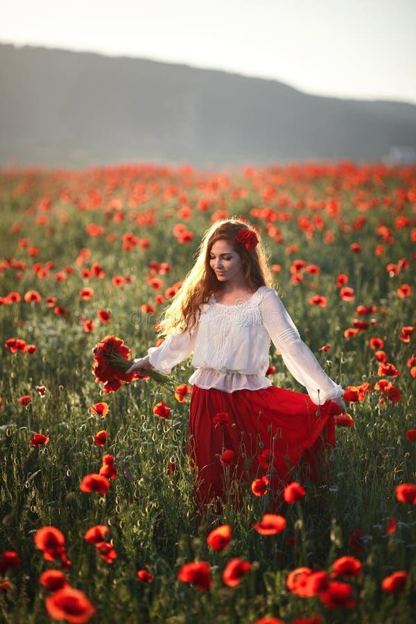 Mujer hermosa joven que camina y que baila a través de un campo de la amapola en la puesta del sol foto de archivo