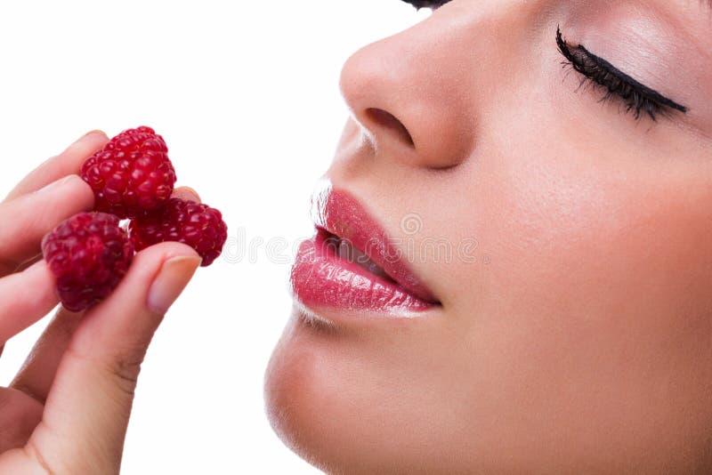 Mujer hermosa joven que come las frambuesas foto de archivo libre de regalías