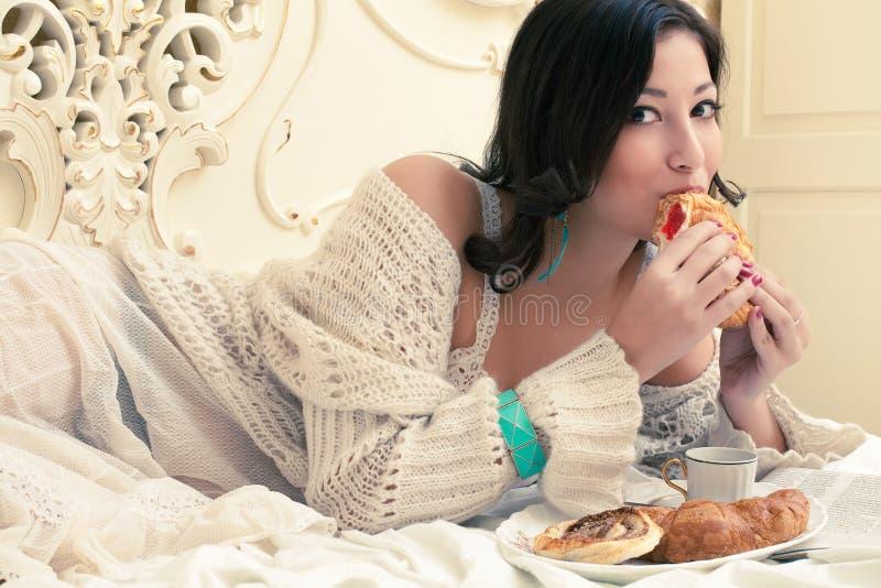 Mujer hermosa joven que come su cruasán con el atasco imagen de archivo