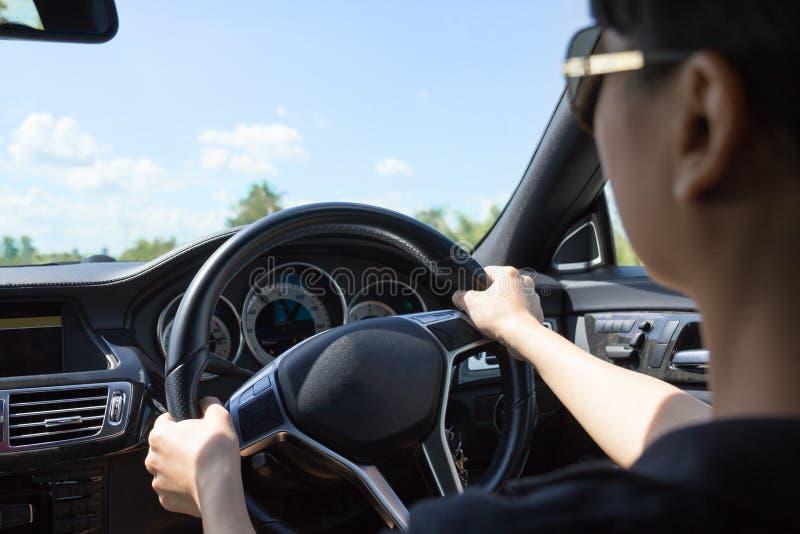 Mujer hermosa joven que conduce un coche de lujo en el camino fotografía de archivo libre de regalías