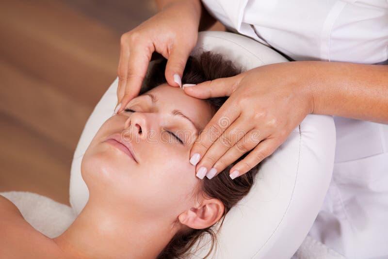 Mujer hermosa joven que consigue masaje facial foto de archivo libre de regalías