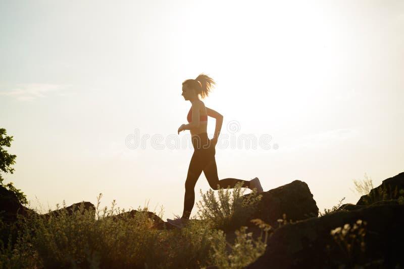 Mujer hermosa joven que corre en el rastro de montaña en la puesta del sol caliente del verano Deporte y forma de vida activa fotos de archivo libres de regalías