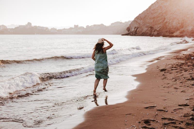 Mujer hermosa joven que corre por la playa en la puesta del sol Rel?jese y concepto de los d?as de fiesta fotografía de archivo