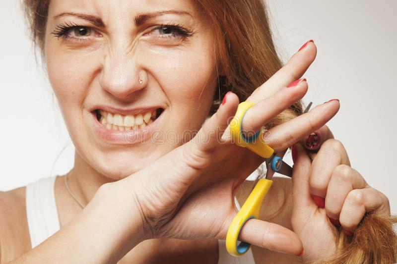 Mujer hermosa joven que corta con esquileos su pelo rubio largo Concepto del cuidado del cabello imagen de archivo libre de regalías