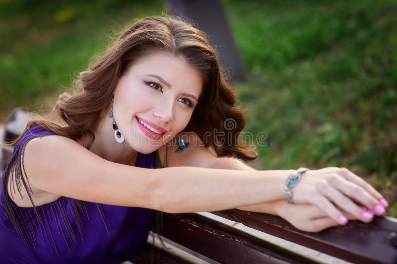 Mujer hermosa joven que descansa sobre un banco en el parque del verano fotos de archivo libres de regalías