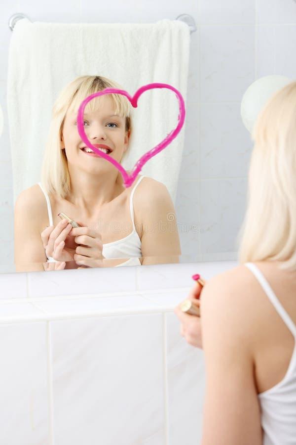 Mujer hermosa joven que drena el corazón grande en el espejo. foto de archivo