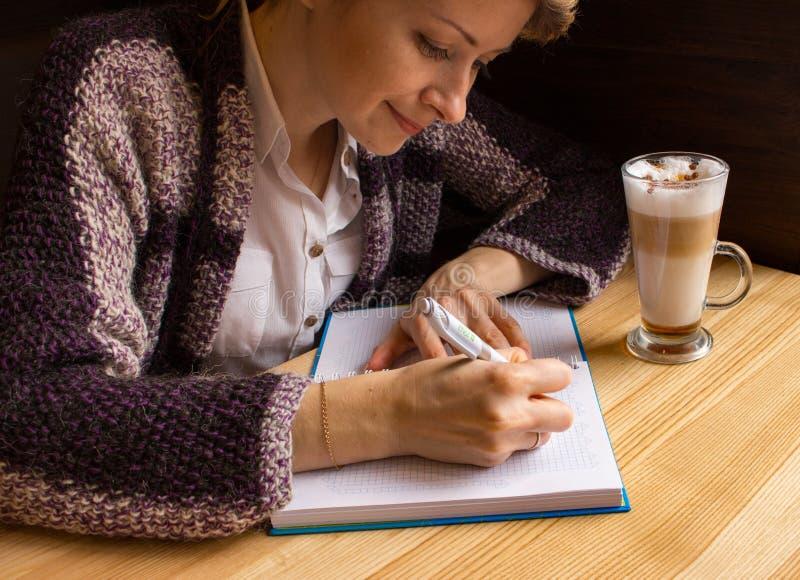 Mujer hermosa joven que escribe con la pluma y el cuaderno abierto en café Concepto del periodista y del escritor foto de archivo