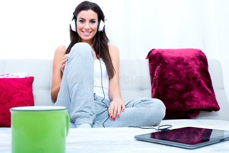 Mujer hermosa joven que escucha la música con un Tablet PC en el hom foto de archivo