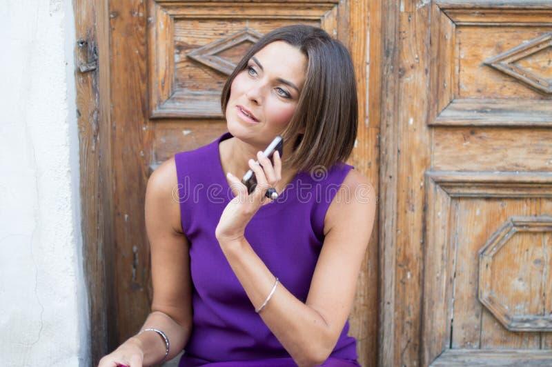 Mujer hermosa joven que habla en el teléfono fotografía de archivo