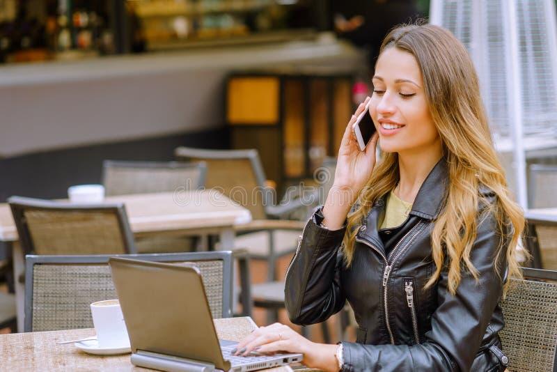 Mujer hermosa joven que habla en el teléfono y que usa el ordenador portátil imagen de archivo libre de regalías
