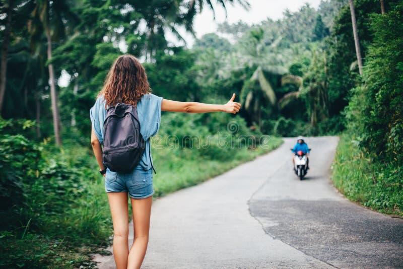 Mujer hermosa joven que hace autostop la colocación en el camino foto de archivo libre de regalías
