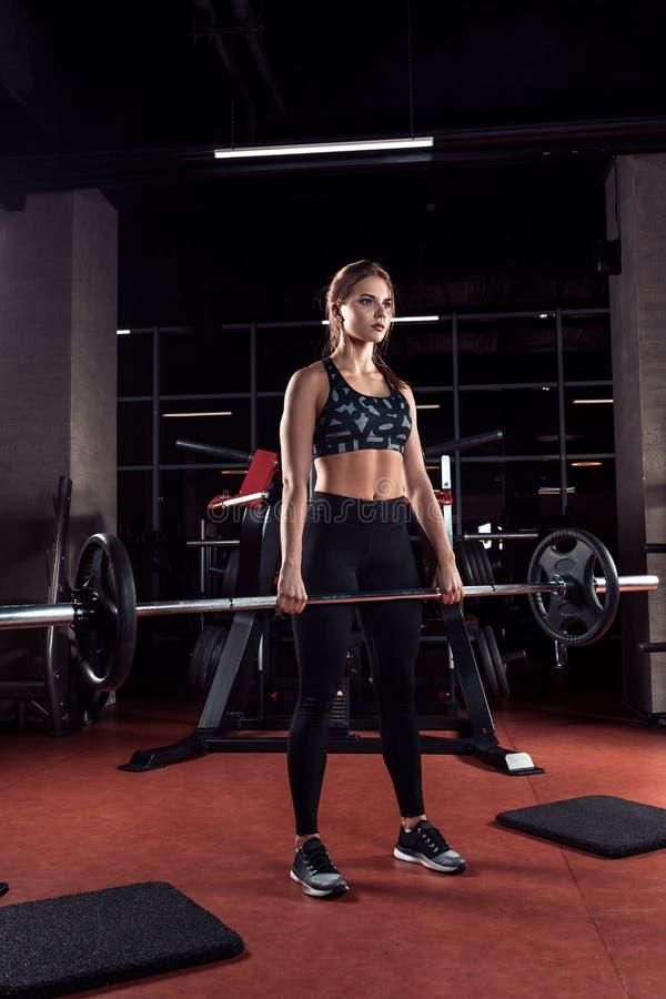 Mujer hermosa joven que hace ejercicio con la barra en un gimnasio Muchacha atlética que hace entrenamiento en un centro de aptit foto de archivo