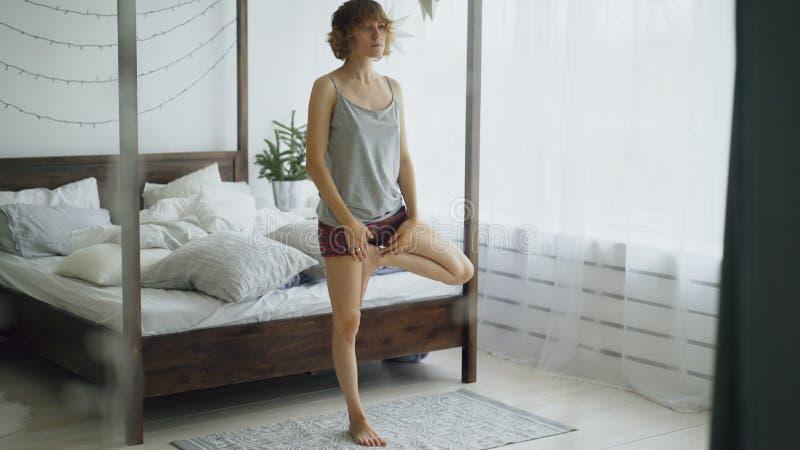 Mujer hermosa joven que hace ejercicio de la yoga cerca de cama en dormitorio en casa foto de archivo