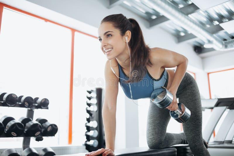 Mujer hermosa joven que hace ejercicios con pesa de gimnasia en gimnasio foto de archivo libre de regalías