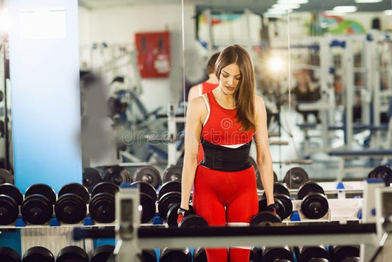 Mujer hermosa joven que hace ejercicios con pesa de gimnasia en gimnasio La muchacha sonriente alegre est? gozando con su proceso imágenes de archivo libres de regalías