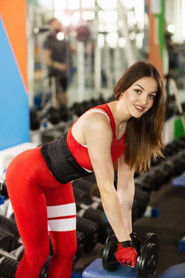 Mujer hermosa joven que hace ejercicios con pesa de gimnasia en gimnasio La muchacha sonriente alegre est? gozando con su proceso fotos de archivo libres de regalías