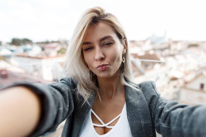 Mujer hermosa joven que hace el selfie en la ciudad fotografía de archivo