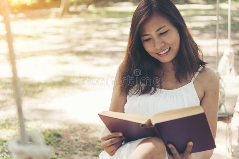 Mujer hermosa joven que lee un libro en el parque con la cara sonriente imágenes de archivo libres de regalías