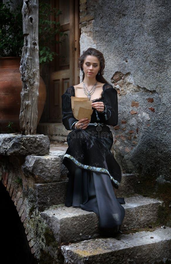 Mujer hermosa joven que lee una letra foto de archivo