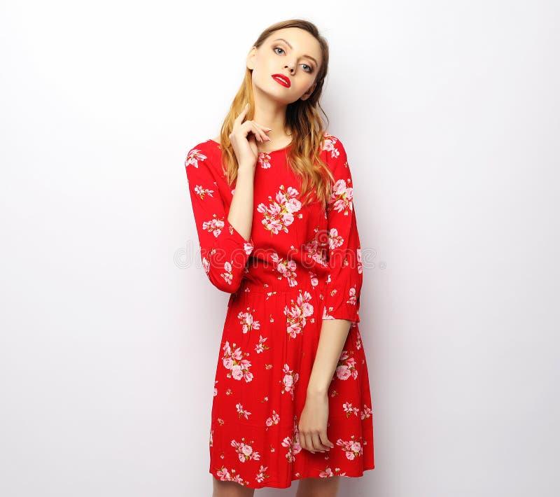Mujer hermosa joven que lleva el vestido rojo que presenta sobre el fondo blanco imagen de archivo
