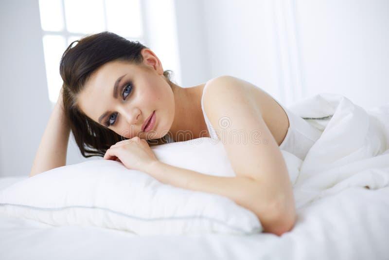 Mujer hermosa joven que miente en cama imagenes de archivo